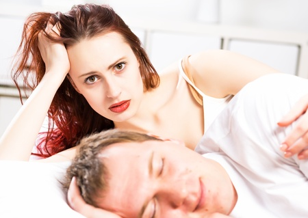 woman sleeping next to her husband in bed, relationship problems people Stock Photo