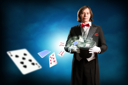 illusionist: magician holding a cylinder, from which fly out of playing cards