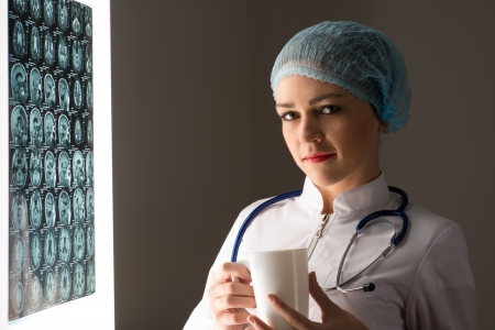 female doctor looking at the x-ray image attached to the glowing screen, holding a white mug with a drink photo