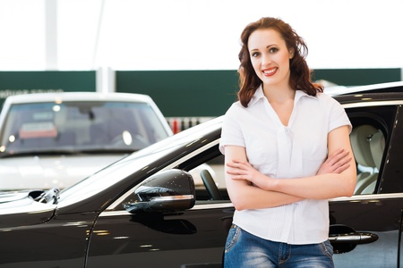 portrait of a young woman stands with his arms crossed over his chest in the cars showroom