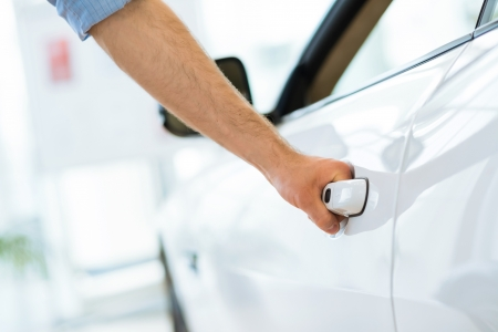 showroom: man opens the door to a new car, car inspection in the showroom Stock Photo