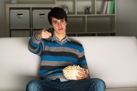 young man watching television with popcorn, remote control switches channels photo