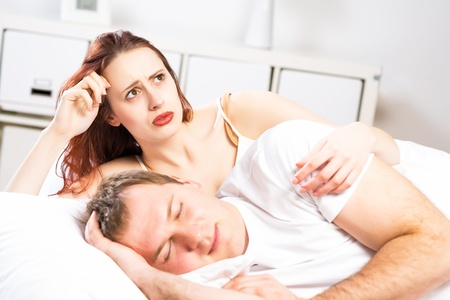 strife: woman sleeping next to her husband in bed, relationship problems people Stock Photo