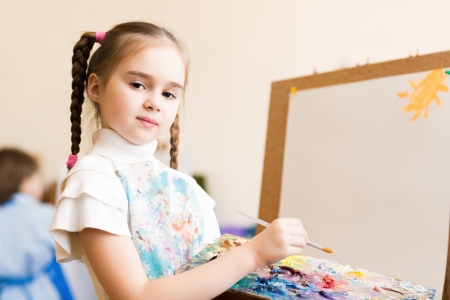 portrait of a girl standing next to his easel, a drawing lesson photo