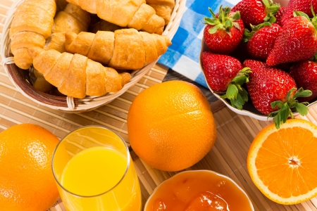 orange juice, croissants and strawberries still life photo