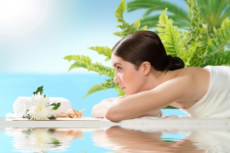 beautiful spa woman lying on the couch, in front of her flower and rolled towel Stock Photo - 20150949