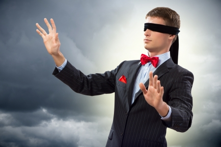 way out: young blindfolded man  his arms and looking for a way out