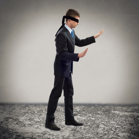 young blindfolded man  his arms and looking for a way out photo