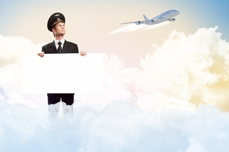 pilot in the form of holding an empty billboard on the background of sky and flying plane photo