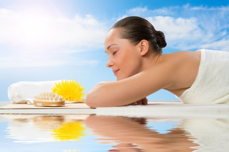 beautiful spa woman lying on the couch, in front of her flower and rolled towel Stock Photo - 20150952