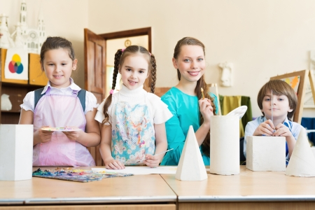 children with the teacher standing at the table, smiling and looking into the cam