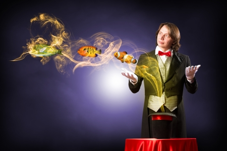 magician casts a spell over the cylinder, circling around the colorful fish photo