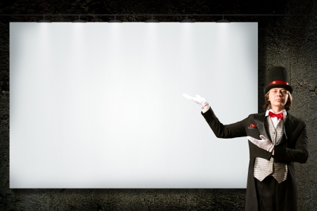 magician in top hat and tie points to the banner, space for text placement photo