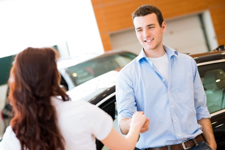woman driving car: man shaking hands with car salesman, buying a new car Stock Photo