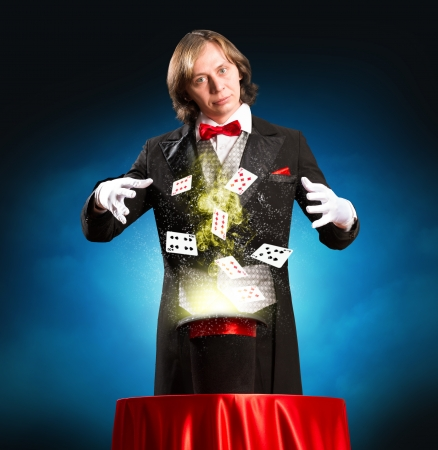 conjuror: magician casts a spell over the cylinder, around the magic and playing cards