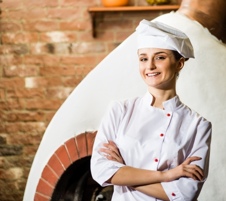 portrait of a cook, is on the traditional kitchen, crossed her arms photo