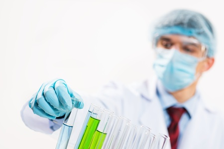 scientist working in the lab, in protective mask and cap, examines a test tube with liquid Stock Photo - 20281348
