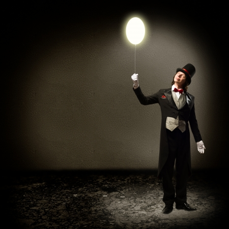 magician in top hat and tie, holding a glowing baloon, and staring at him Stock Photo - 20324472