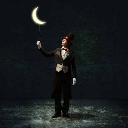 magician in top hat and tie, holding a glowing moon on a string Stock Photo - 20331291