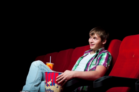 man in a movie theater, watching a movie and drink a drink photo