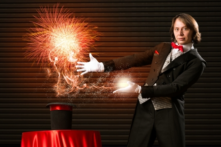wizard casts a spell over his hat from the hat off smoke, colored lights and magic