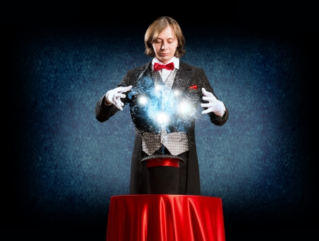 magic young: wizard casts a spell over his hat from the hat off smoke, colored lights and magic