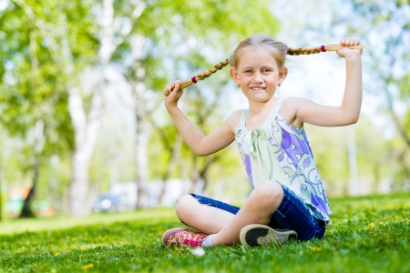 Girl in the park sitting on the grass and keeps himself pigtails photo