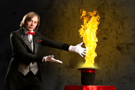 magician conjures a stream of fire out of the hat photo
