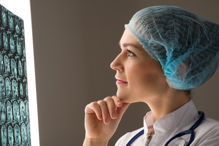 female doctor looking at the x-ray image attached to the glowing screen photo
