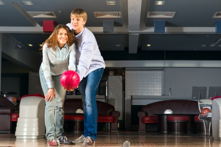 guy hugs her friendgirl, playing together in bowling photo