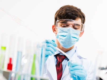 Portrait of a scientist working in the lab examines a test tube with liquid Stock Photo - 20564194