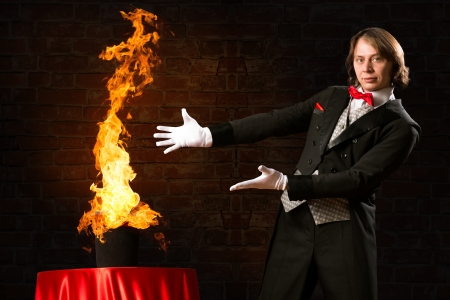 magician conjures a stream of fire out of the hat Stock Photo