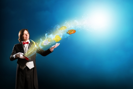 magician produces a cylinder of magic and little fishes Stock Photo - 20678540