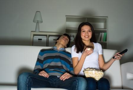 humoristic: mujer viendo la televisi�n con entusiasmo, su marido est� durmiendo al lado del sof� Foto de archivo
