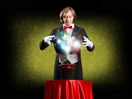 paranormal: wizard casts a spell over his hat from the hat off smoke, colored lights and magic