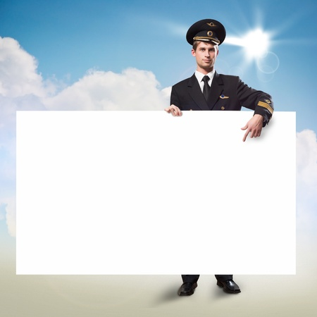 pilot in the form of holding an empty billboard on the background of sky with clouds, place for text photo
