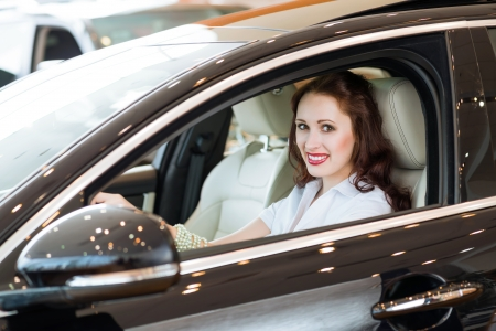 l hand: young woman in the new car in the showroom, smiling and looking in camera Stock Photo