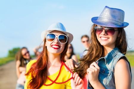 Twee jonge meisjes plezier op de achtergrond van blauwe hemel en vrienden