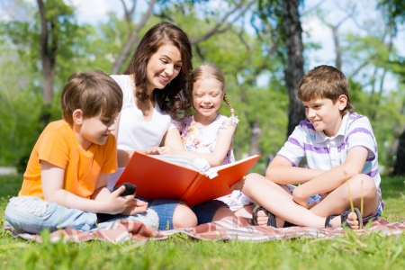 children and teacher reading book together in the summer park photo
