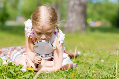 investigating: girl in the park with a magnifying glass considers plants