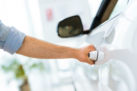man opens the door to a new car, car inspection in the showroom Stock Photo - 20824562