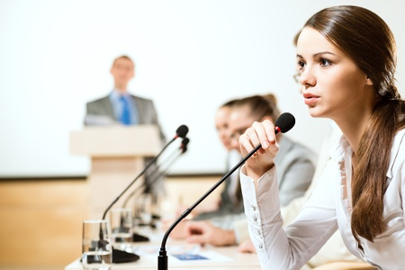 Business woman speaks into a microphone, communication businessmen at a conference photo