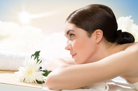 beautiful spa woman lying on the couch, in front of her flower and rolled towel Stock Photo - 20771937
