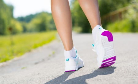 athlete s feet, close-up run on the asphalt road in a summer park Stock Photo
