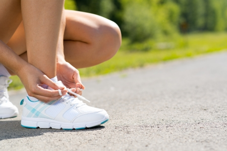 female runner tying lace on sports shoes, training for a marathon