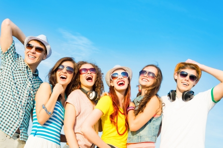 friends party: group of young people wearing sunglasses and hats hugging and standing in a row, spending time with friends