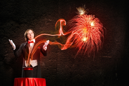 conjuror: wizard casts a spell over his hat from the hat off smoke, colored lights and magic