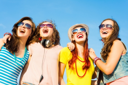 cool girl: group of young people wearing sunglasses and hats hugging and standing in a row, spending time with friends