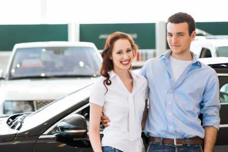 Young couple standing embracing near a car in the showroom photo