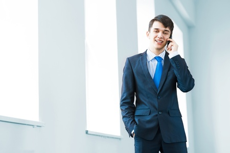 Portrait of a young successful businessman in bright office, talking on cell phone photo